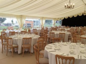 inside of marquee with wooden chairs